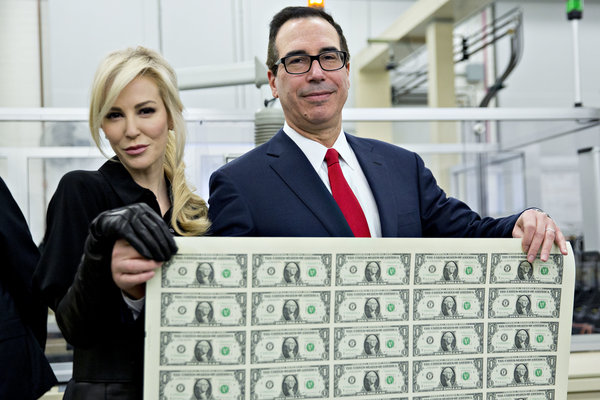 """Steven Mnuchin, U.S. Treasury secretary, right, and his wife Louise Linton hold a 2017 50 subject uncut sheet of $1 dollar notes bearing Mnuchin's name for a photograph at the U.S. Bureau of Engraving and Printing in Washington, D.C., U.S., on Wednesday, Nov. 15, 2017. A change in the Senate tax-overhaul plan that would expand a temporary income-tax break for partnerships, limited liability companies and other so-called """"pass-through"""" businesses won the endorsement of a national small-business group today. Photographer: Andrew Harrer/Bloomberg via Getty Images"""