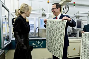 """Steven Mnuchin, U.S. Treasury secretary, right, displays a 2017 50 subject uncut sheet of $1 dollar notes bearing Mnuchin's name for his wife Louise Linton at the U.S. Bureau of Engraving and Printing in Washington, D.C., U.S., on Wednesday, Nov. 15, 2017. A change in the Senate tax-overhaul plan that would expand a temporary income-tax break for partnerships, limited liability companies and other so-called """"pass-through"""" businesses won the endorsement of a national small-business group today. Photographer: Andrew Harrer/Bloomberg via Getty Images"""